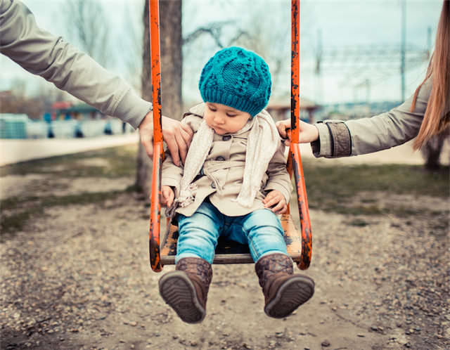Foto representando el concepto de divorcio con relación a los hijo y en especial  la custodia compartidas. Muestra a un niño o niña de unos dos años en un columpio con la mano de la madre a un lado y la del padre a otro.