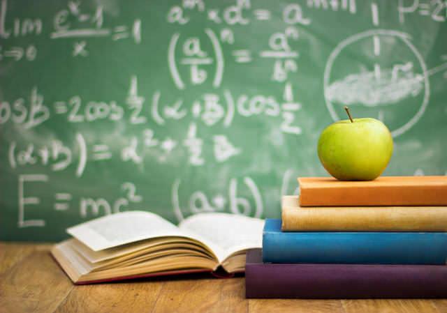 Unos libros de texto y una manzana, con una pizarra llena de fórmulas matemáticas como fondo, representan el inicio del año escolar, mediante fotografía.